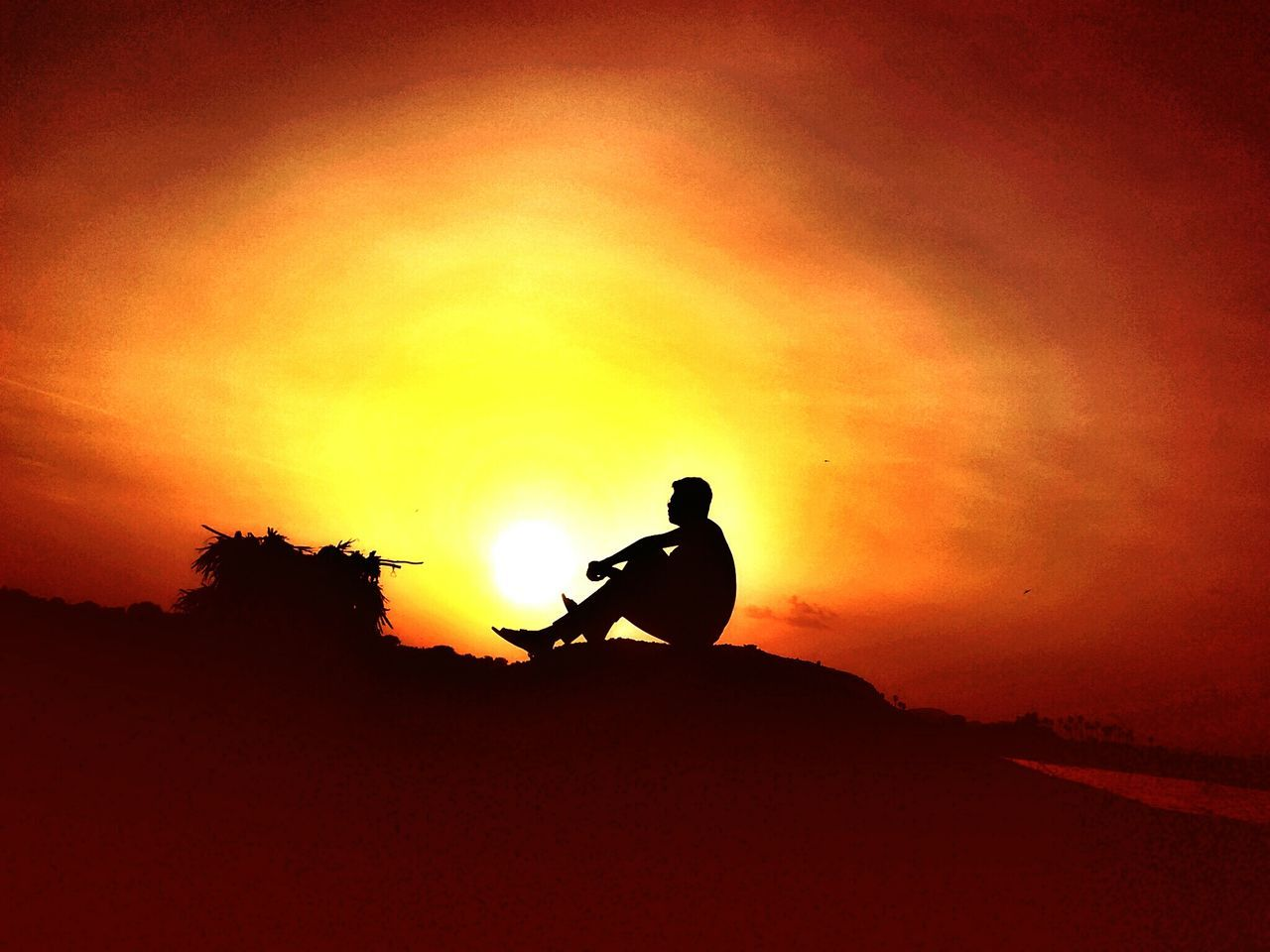 Silhouette Of Person Sitting On Rock