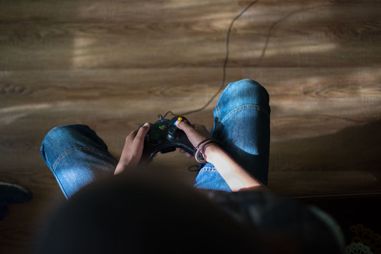 Gamer Gaming Body Part Casual Clothing Communication Flooring Game Controller Hardwood Floor Human Body Part Human Leg Indoors  Jeans Lifestyles Low Section One Person Personal Perspective Real People Selective Focus Shoe Sitting Technology Wireless Technology Wood