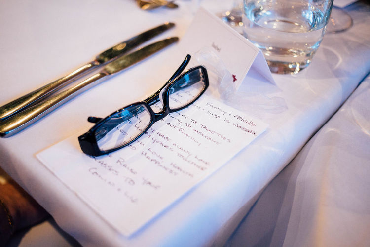 Close-up of eyeglasses by note on table