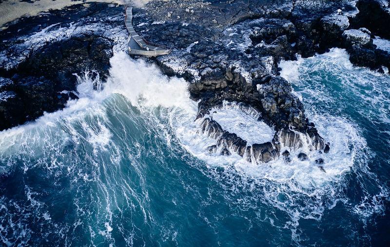 High angle view of sea waves splashing on rock