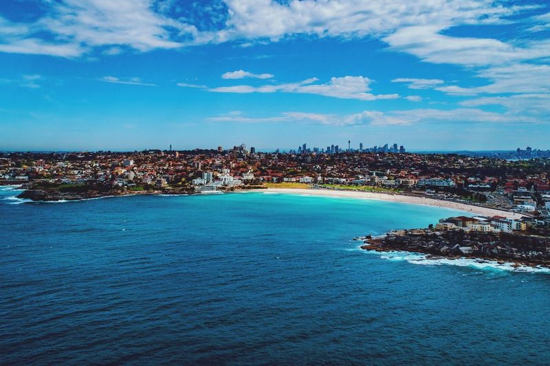 Bondi & The City Available as fine art print on www.kess.gallery #bondi #sydney Sky Cloud - Sky Blue Building Exterior Architecture Water Built Structure City Nature Sea Scenics - Nature Tranquility Day No People Beauty In Nature Waterfront Outdoors Tranquil Scene Building Cityscape