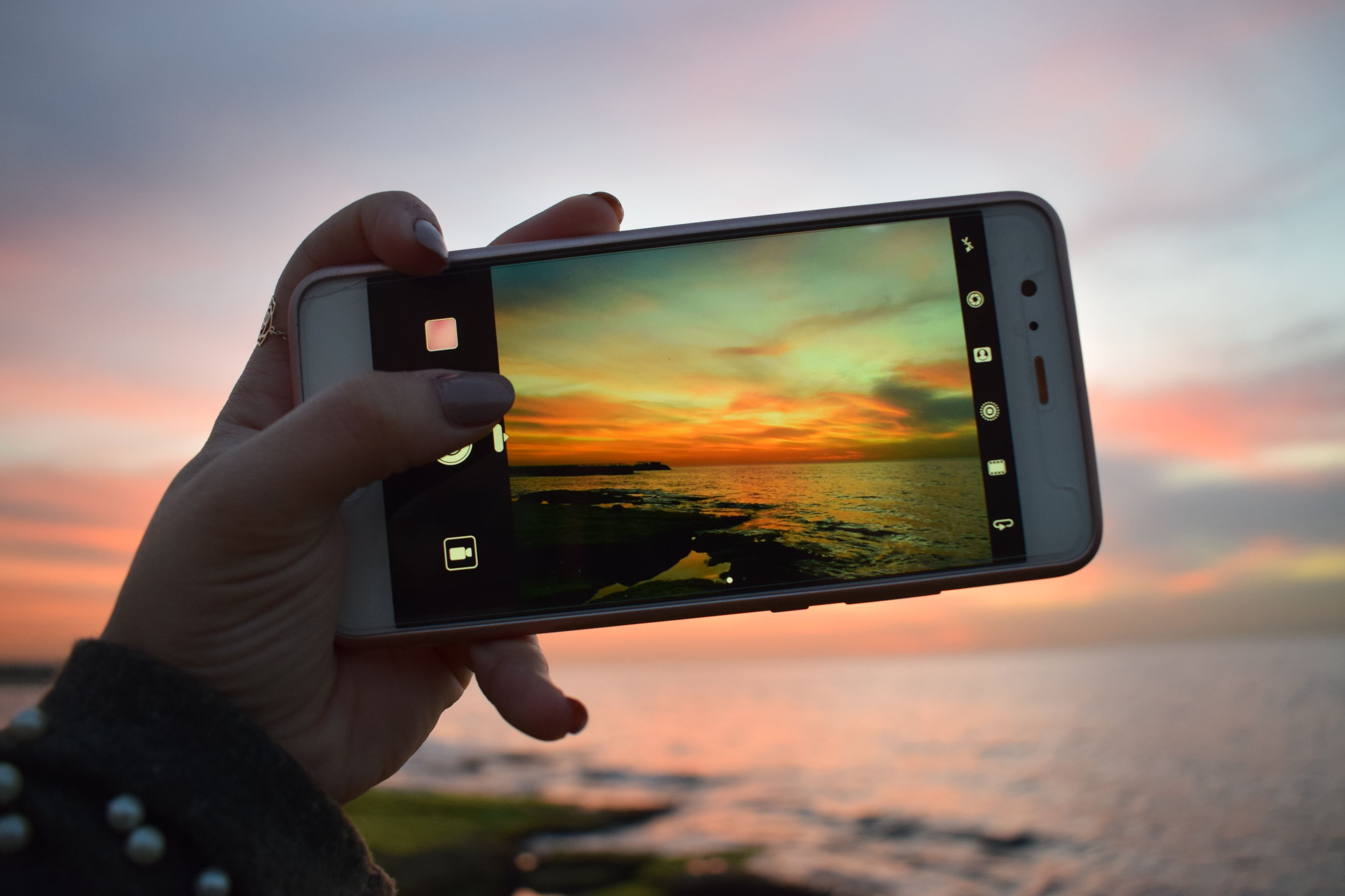 technology, human hand, holding, wireless technology, sunset, hand, one person, photography themes, sky, portable information device, smart phone, mobile phone, communication, human body part, real people, screen, telephone, using phone, photographing, leisure activity, outdoors, digital camera, finger