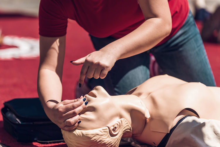 Low section of woman demonstrating on cpr dummy