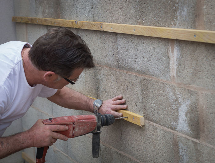 Carpenter drilling on wall
