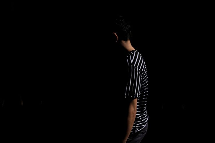 Side view of man standing against black background