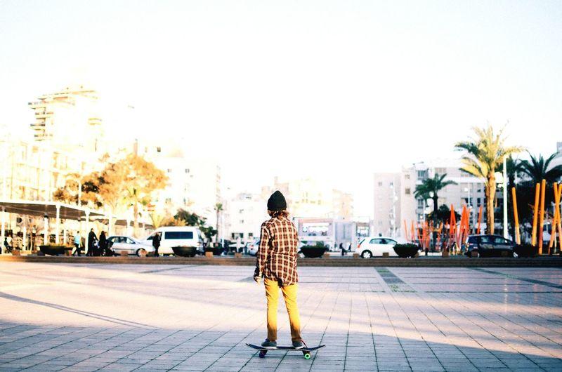 Rear View Of Teenage Boy Skateboarding