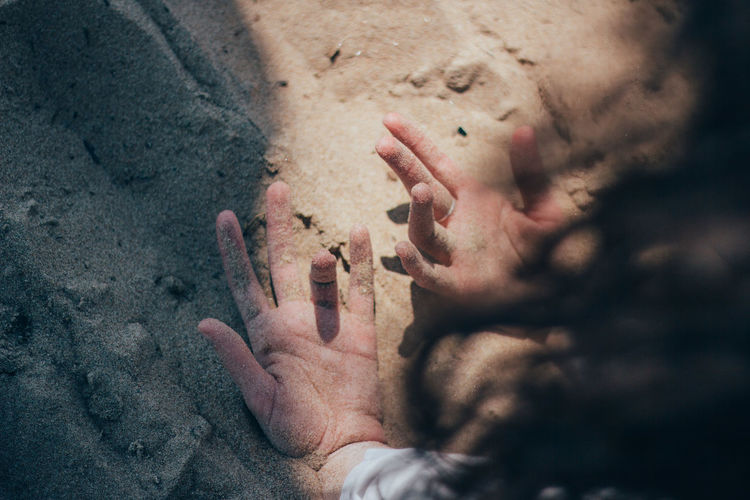Cropped hands of woman on sand at beach