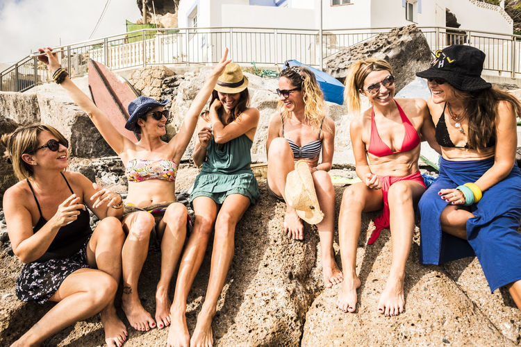 High angle view of friends wearing bikinis sitting on rock formation during sunny day