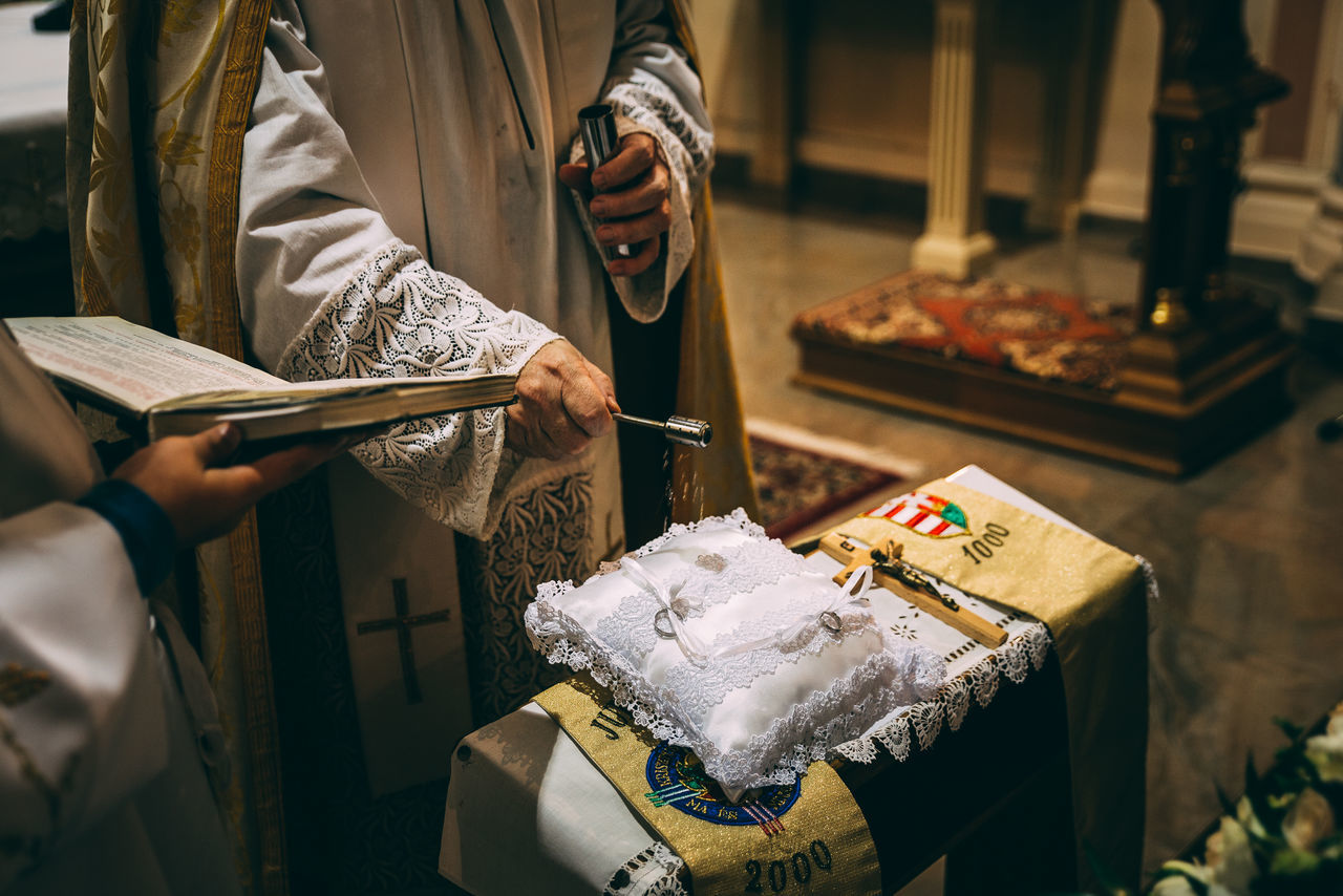 Priest sprinkling holy water on wedding rings at church