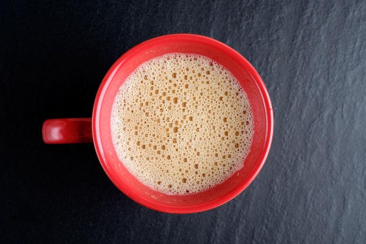 Top view of teh tarik (Malaysian Pull Tea) or milk tea in red mug. Asian  Red Teh Tarik Teh Tarik (Malaysian Pull Tea) Culture Drink Milk Coffee Milk Tea Mug Popular Drink In Malaysia Top View