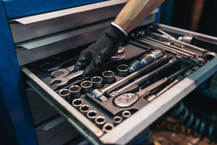 Cropped hand of man holding wrench in tool box