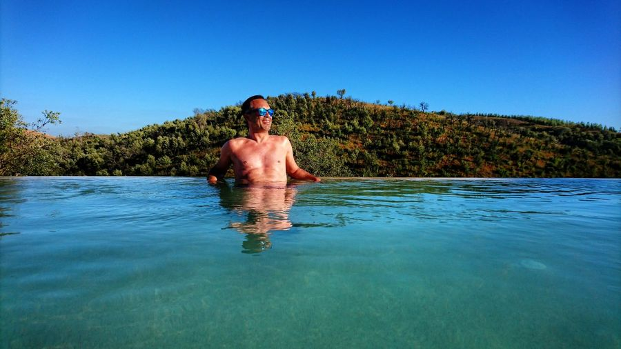 Shirtless mature man swimming in infinity pool against clear sky