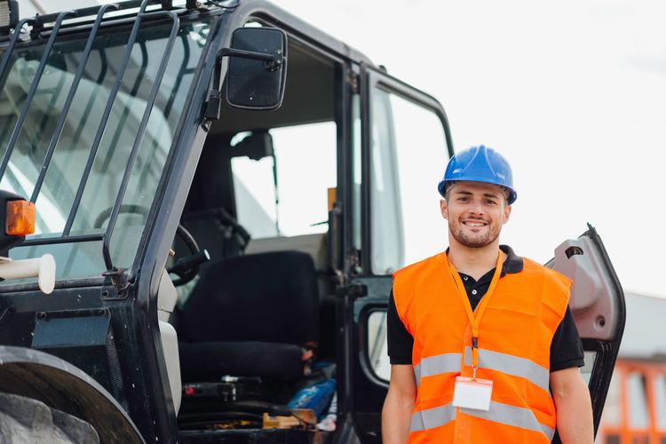Portrait construction worker standing by crane