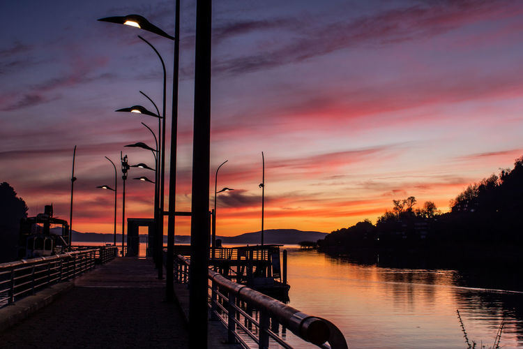 Silhouette street by lake against sky during sunset