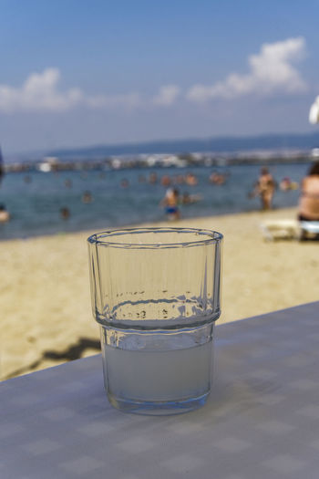 Greek tavern alcoholic drink. Ouzo on the rocks served on a glass in blurred beach background. Greek Taverna Summer In Greece Alcohol Alcoholic Drink Drinking Glass Food And Drink Glass Greece Greek Beach Greek Drink Greek Ouzo Greek Tavern Horizon Over Water Ouzo Ouzo Alcoholic Drink Ouzo Beach Greece Ouzo Glass Ouzo With Ice Tavern  Tavern On Beach Tavern Table Tavern Tables Taverna Tsipouro Vacation