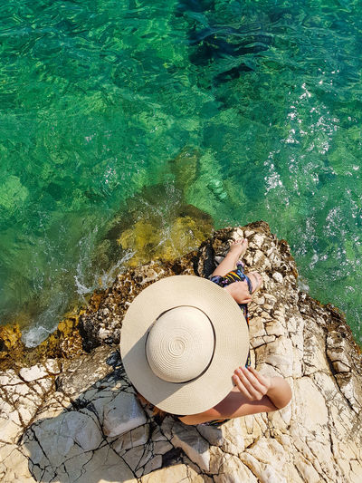 High angle view of woman on rock at beach. summer, lifestyle, sea, hat, overhead.