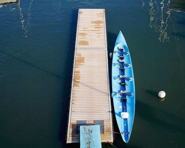 Deserted dock with blue rowing canoe. Sport Timber Water Sea Rowing Boat Water Sea Wood - Material High Angle View Nature Day Transportation Tranquility Travel Sunlight Outdoors Pier Blue No People Mode Of Transportation Yacht