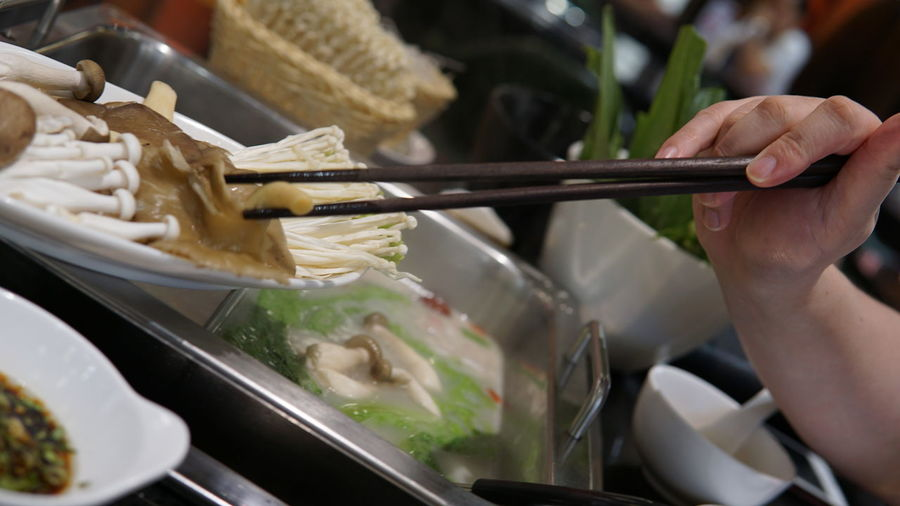 Cooking Dinner Eating Chinese Food Chopsticks Freshness Hand Hand Movement Healthy Eating Hotpot Mushroom Preparation  Preparing Food Raw Food