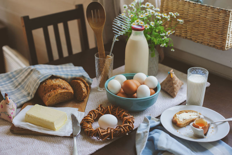 country breakfast on rustic home kitchen with farm eggs, butter, wholegrain bread and milk. Organic homemade food, easter concept. Breakfast Easter Egg Table Food Countryside Farm Farm Life Organic Food Bread Eating Morning Milk Chicken Decoration Spring Homemade Wholegrain Healthy Eating