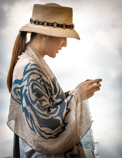Stylish Woman Texting Against Sky