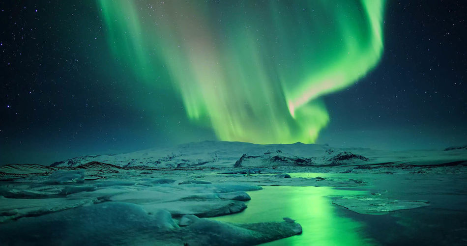 Scenic view of aurora borealis over landscape against sky at night