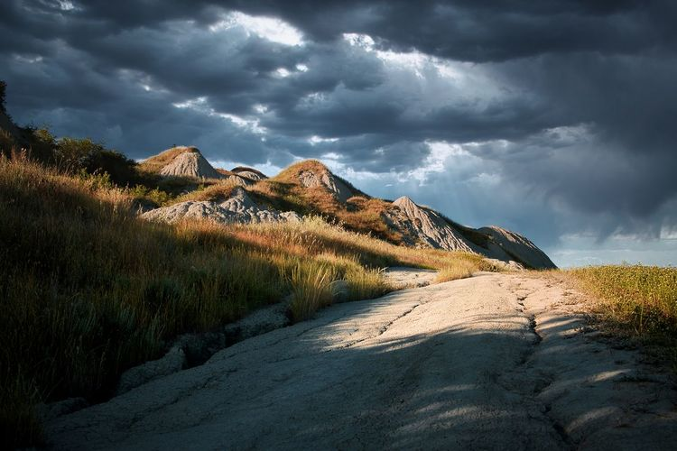 Scenic view of  tuscany clay hills under dramatic skies. a white pathway.   solitary place