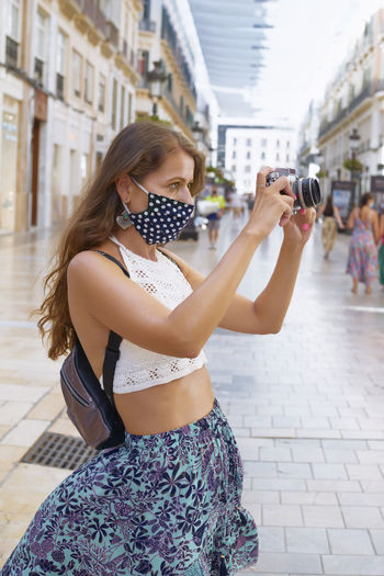 Midsection of woman photographing with mobile phone while standing on street