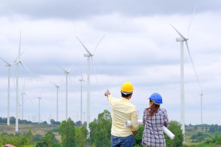 People on wind turbines against sky