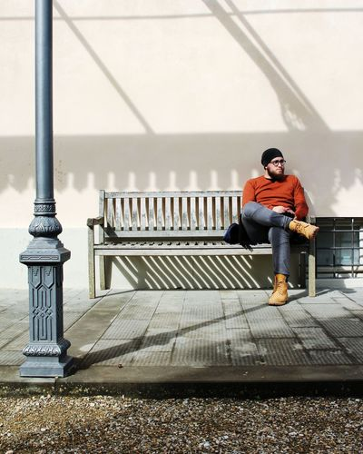 Full Length Of Man Sitting On Bench