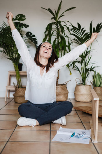 Woman sitting on potted plant at home