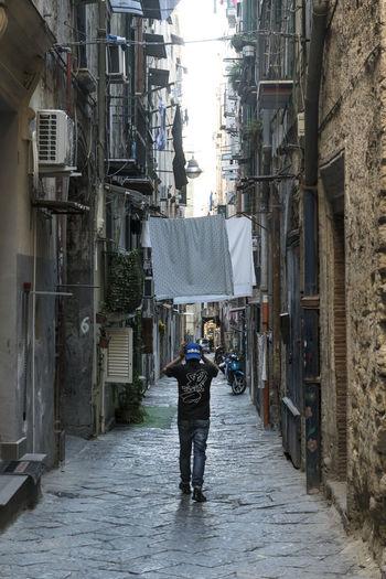 Rear view of man walking on wet street in city