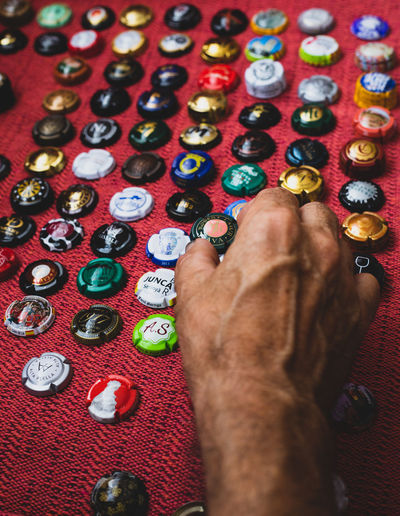 champagne bottle caps Bottle Cap Art And Craft Body Part Choice Close-up Finger Hand High Angle View Human Body Part Human Hand Human Limb Indoors  Large Group Of Objects Leisure Activity Lifestyles Men Multi Colored One Person Personal Perspective Real People Relaxation Variation