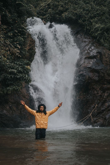 Portrait of man with arms raised standing against waterfall