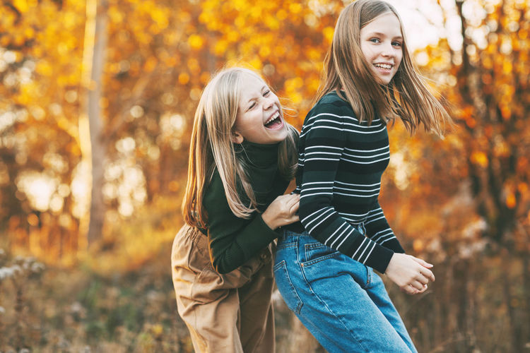 Two happy girls sisters laughing, having fun and playing in the fall in nature outdoors