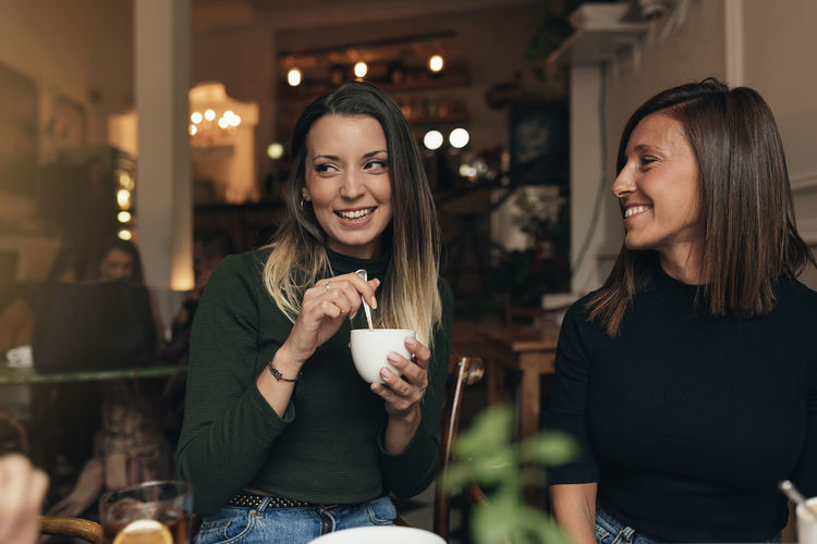 Drink Food And Drink Smiling Refreshment Happiness Young Adult Women Young Women Real People Cup Leisure Activity Casual Clothing Adult Coffee - Drink Lifestyles Friendship Two People Mug Restaurant Long Hair Hairstyle Drinking Hair Hot Drink Beautiful Woman