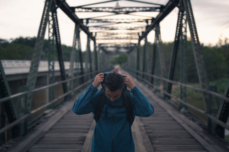 Young man backpacker walking cross the bridge and wearing hoodie  , freedom and recreation concept