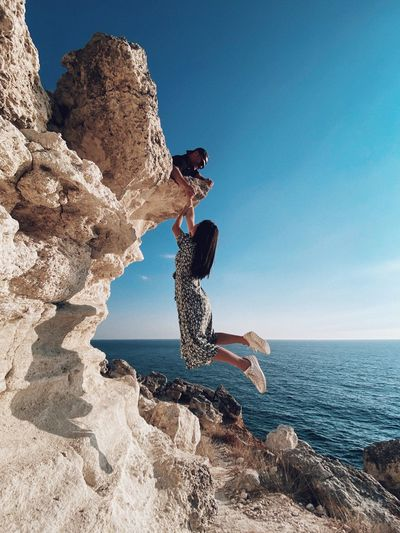 Full length of woman holding hand mid-air by rock formation against sky and sea