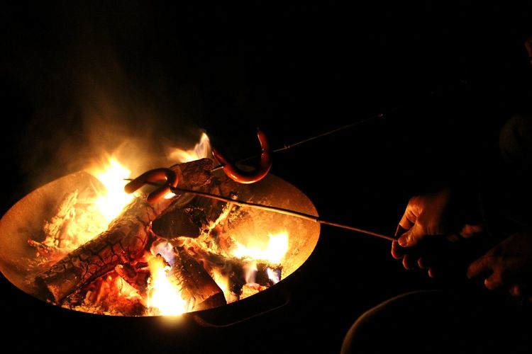 Cropped hand preparing sausage in bonfire at night