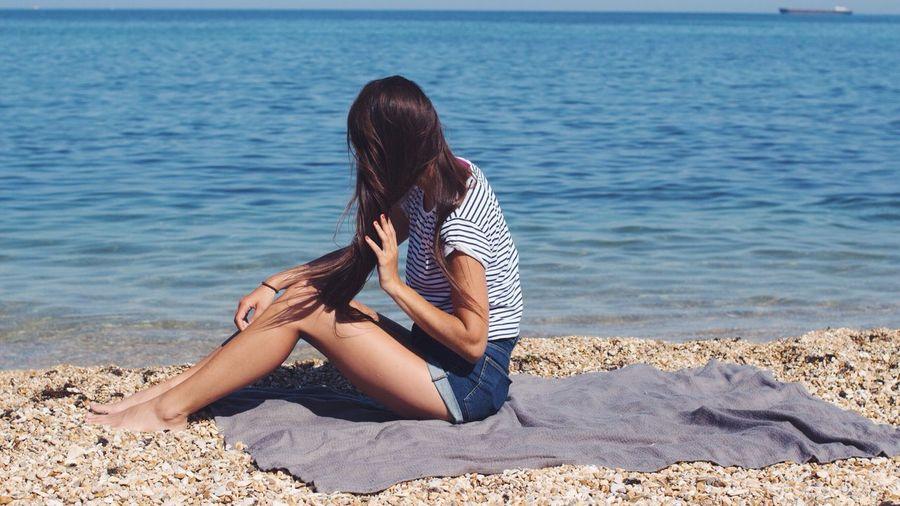 Woman Sitting On Beach By Sea