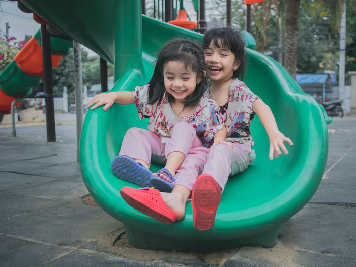 Full length of happy sisters sliding in playground