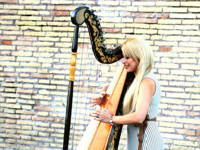 Woman Playing Harp Against Wall