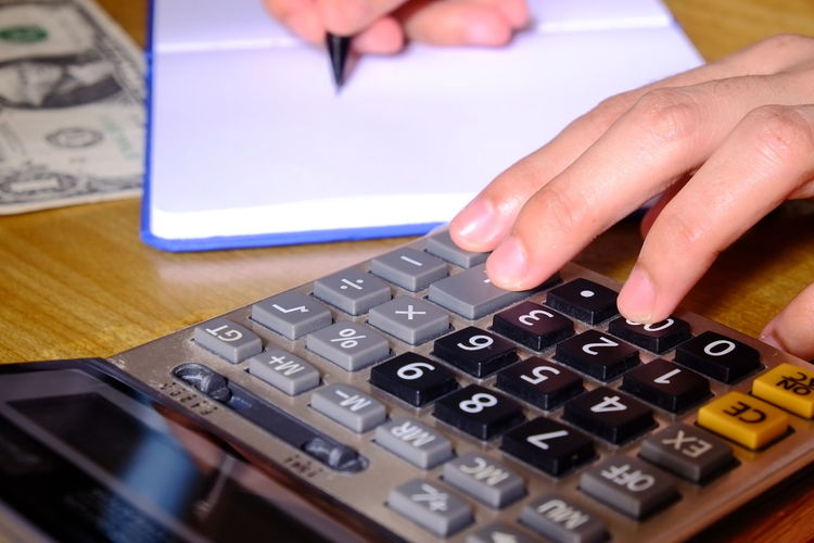 Cropped hands of man calculating on table
