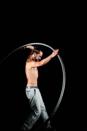 Circus Adult Arms Raised Black Background Circle Copy Space Geometric Shape Holding Human Arm Human Body Part Indoors  Men Motion One Person Plastic Hoop Shirtless Skill  Standing Studio Shot Three Quarter Length Young Adult