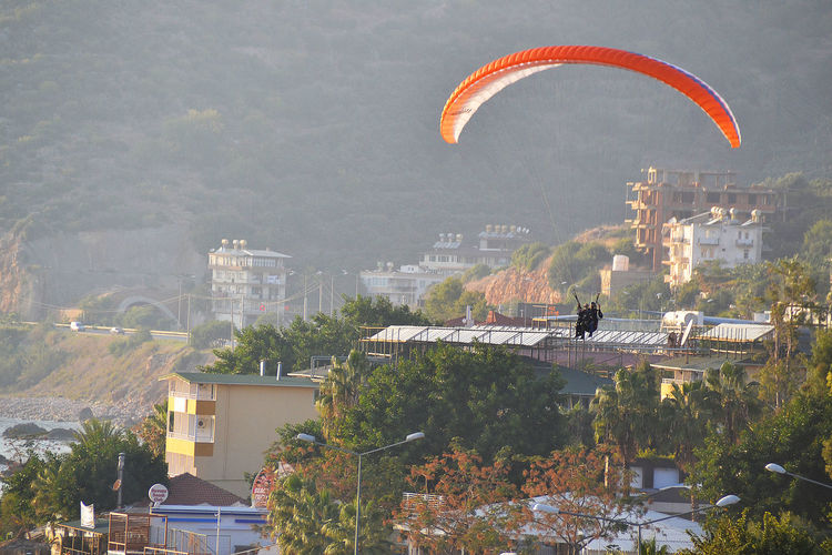 Two people in paraglider mid-air