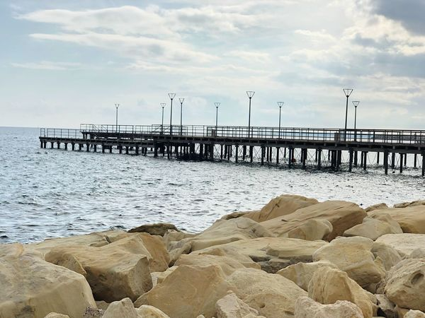 Waves Water Rocks Beauty Art Sunlight Shapes Clouds Wharf Pier Water Sea Sky Beach Land Beauty In Nature Nature Scenics - Nature Pier Tranquility Built Structure Rock Horizon Over Water Tranquil Scene Cloud - Sky Day Outdoors Architecture Solid No People