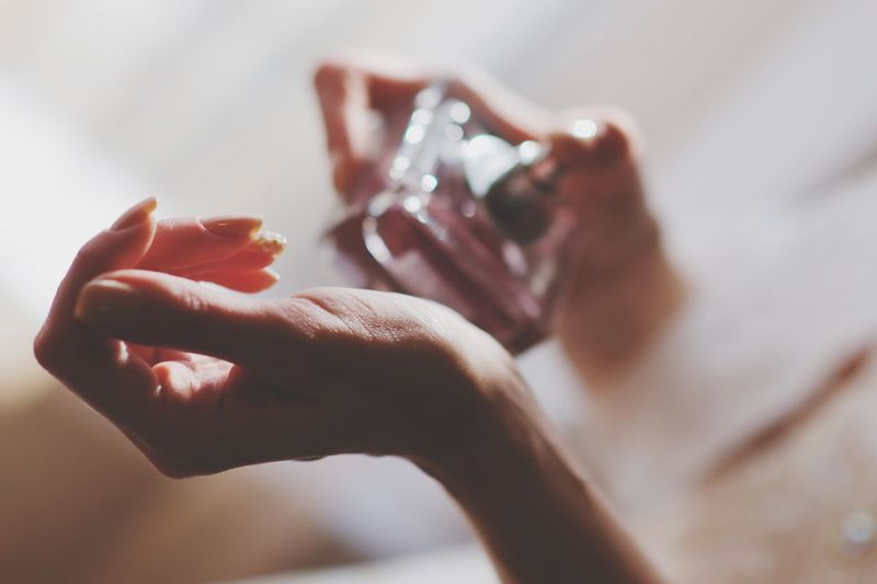 Cropped hands of woman applying perfume