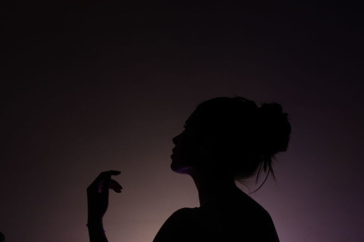 Silhouette woman looking away against colored background