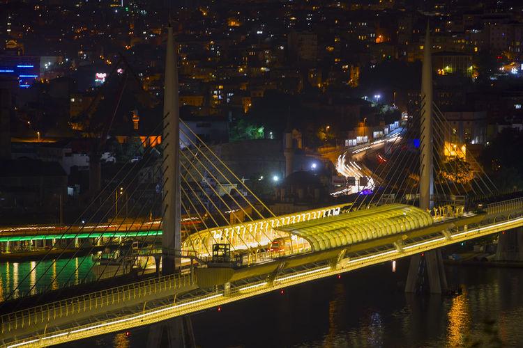 Illuminated railway bridge over river at night