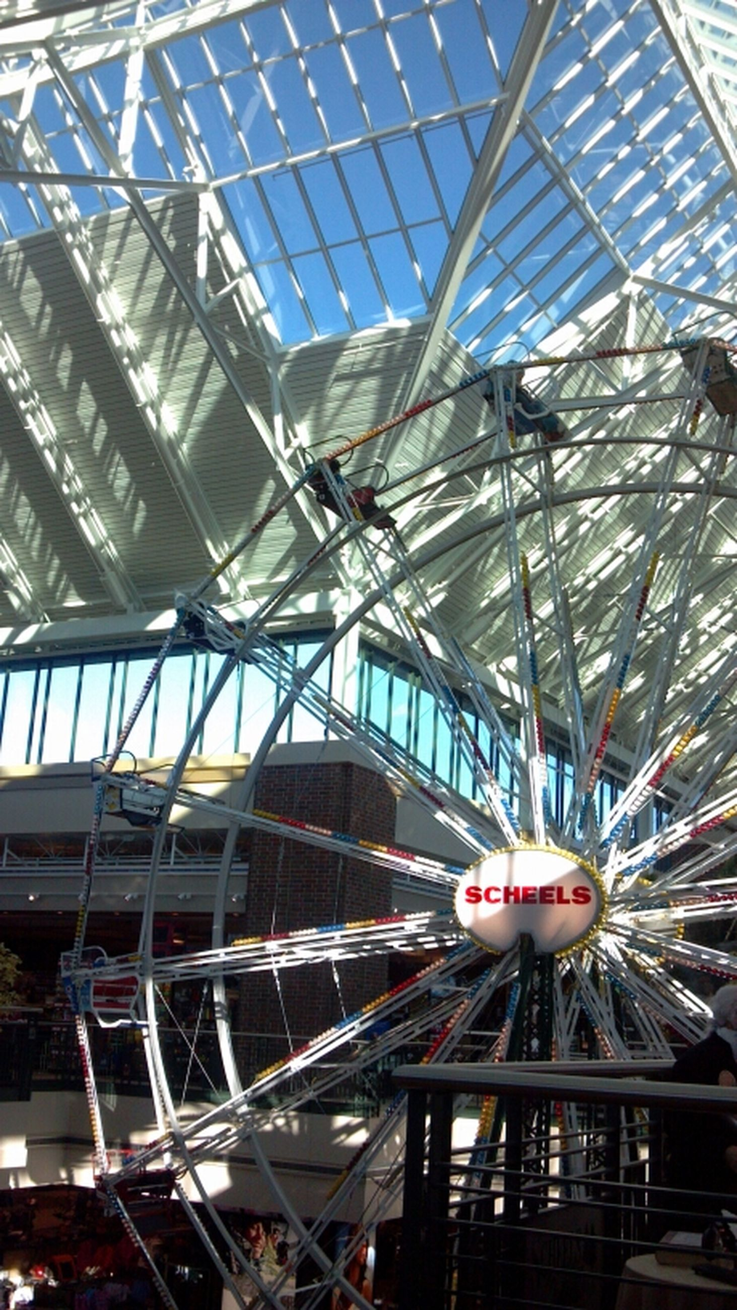 built structure, architecture, low angle view, indoors, building exterior, metal, glass - material, ceiling, amusement park, modern, city, incidental people, day, amusement park ride, ferris wheel, metallic, arts culture and entertainment, high angle view, travel, building