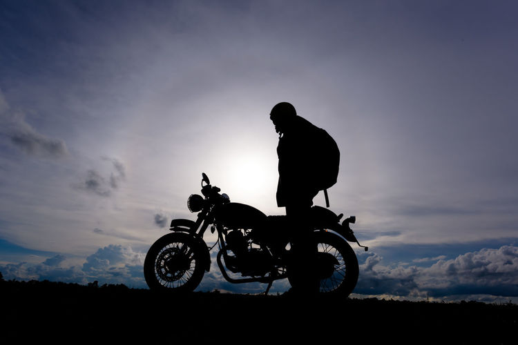 Silhouette Biker With Motorcycle Standing On Landscape Against Sky During Sunset